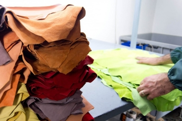 Photo of several samples of processed and treated animal skins on a work table, for the industrial p