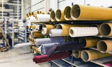 Photo of fabric rolls stacked on a work table inside a warehouse in a textile industry. Industrial w